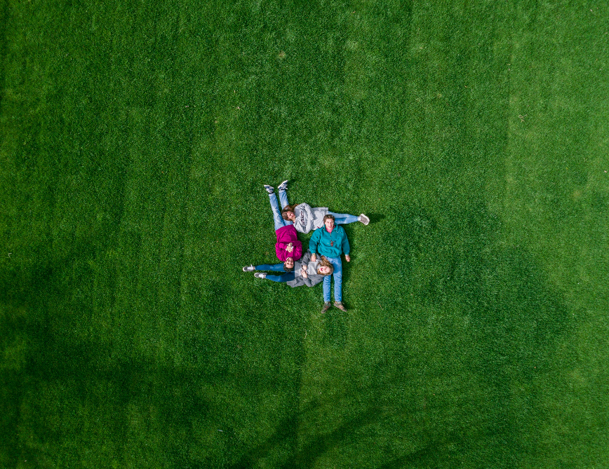 friends forming a hashtag sign on the grass