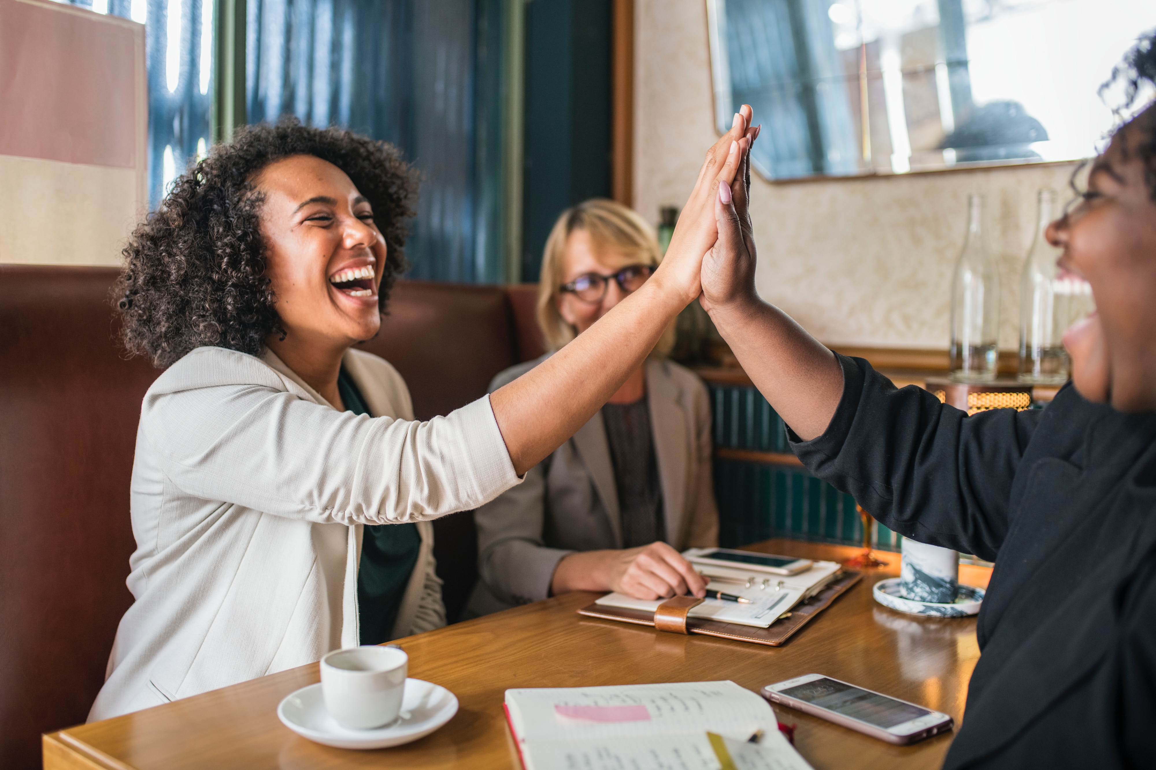 Two woman high five in a cafe