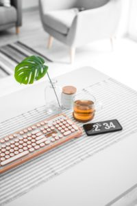 desk with keyboard, whiskey in a short glass next to keyboard. Phone displaying 2:34 on clock and one small leaf in a clear vase