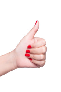 Female hand with red nail gesture good sign isolated on white background