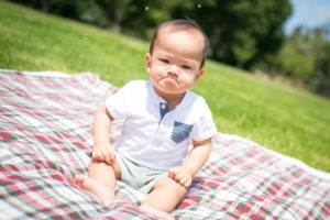frowning baby sitting on a picnic blanket
