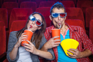 spectators sitting in the cinema and watching movie with cups of cola and popcorn