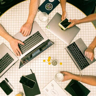 A desk with four laptops, three notebooks, iPhones, and people's arms on a desk are shown from a bird's eye view.