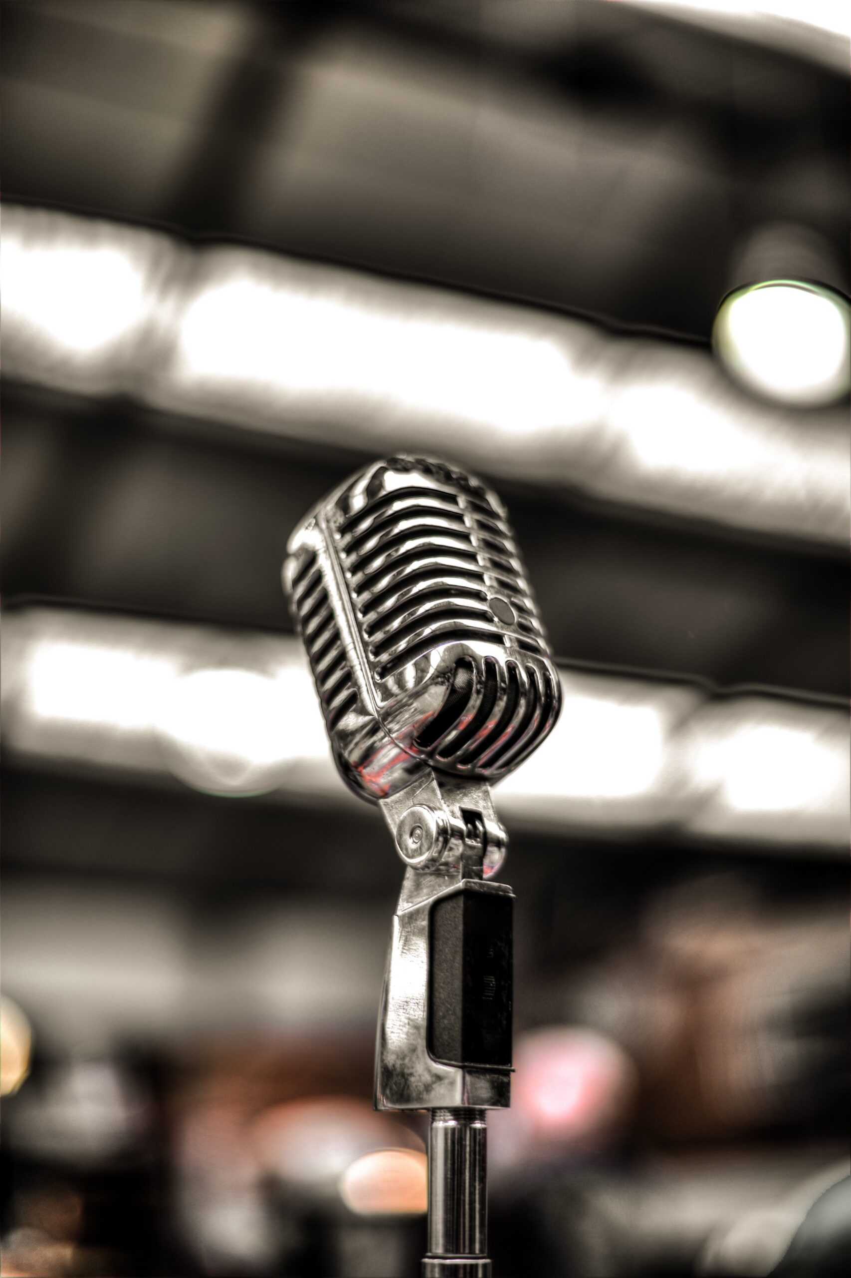 An old-fashioned microphone is shown in the foreground with a blurred background