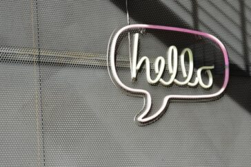 neon sign on plain wall displaying the word hello inside a speech bubble