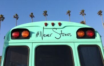 turquoise bus in front of palm trees with the phrase # never stress on back