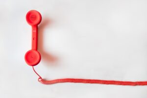 a red telephone with a cord appears flat lay style on a white backdrop
