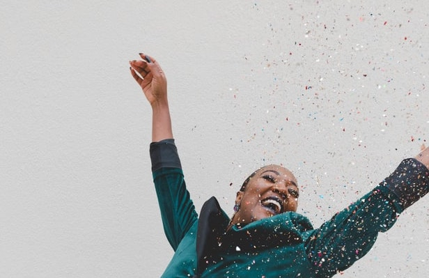 woman proudly waving arms in the air while confetti falls