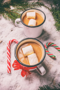 Two mugs of hot cocoa with large marshmallows sit on the snow surrounded by pine needles and candy canes.