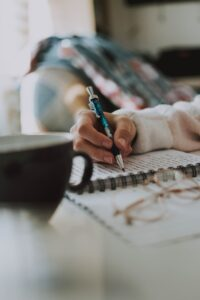 A woman holds a pen as she crafts her brand tone in a notebook with a coffee mug nearby.