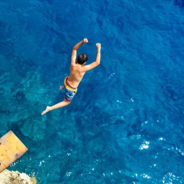 man plunging into blue ocean water