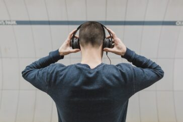 man holding earphones to his ears - clubhouse social media app
