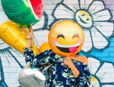 woman holding emoji balloons in front of an art mural