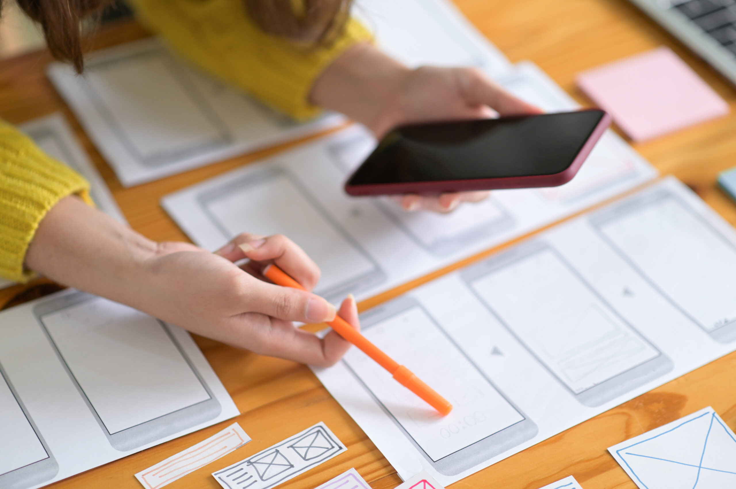 Web designers hold a smartphone as they draw out what the mobile website will look like