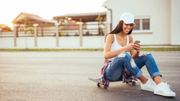 girl answering Instagram DMs on a skateboard