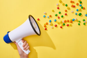 a woman holds a megaphone on a yellow background; the megaphone has rainbow candy coming out of it