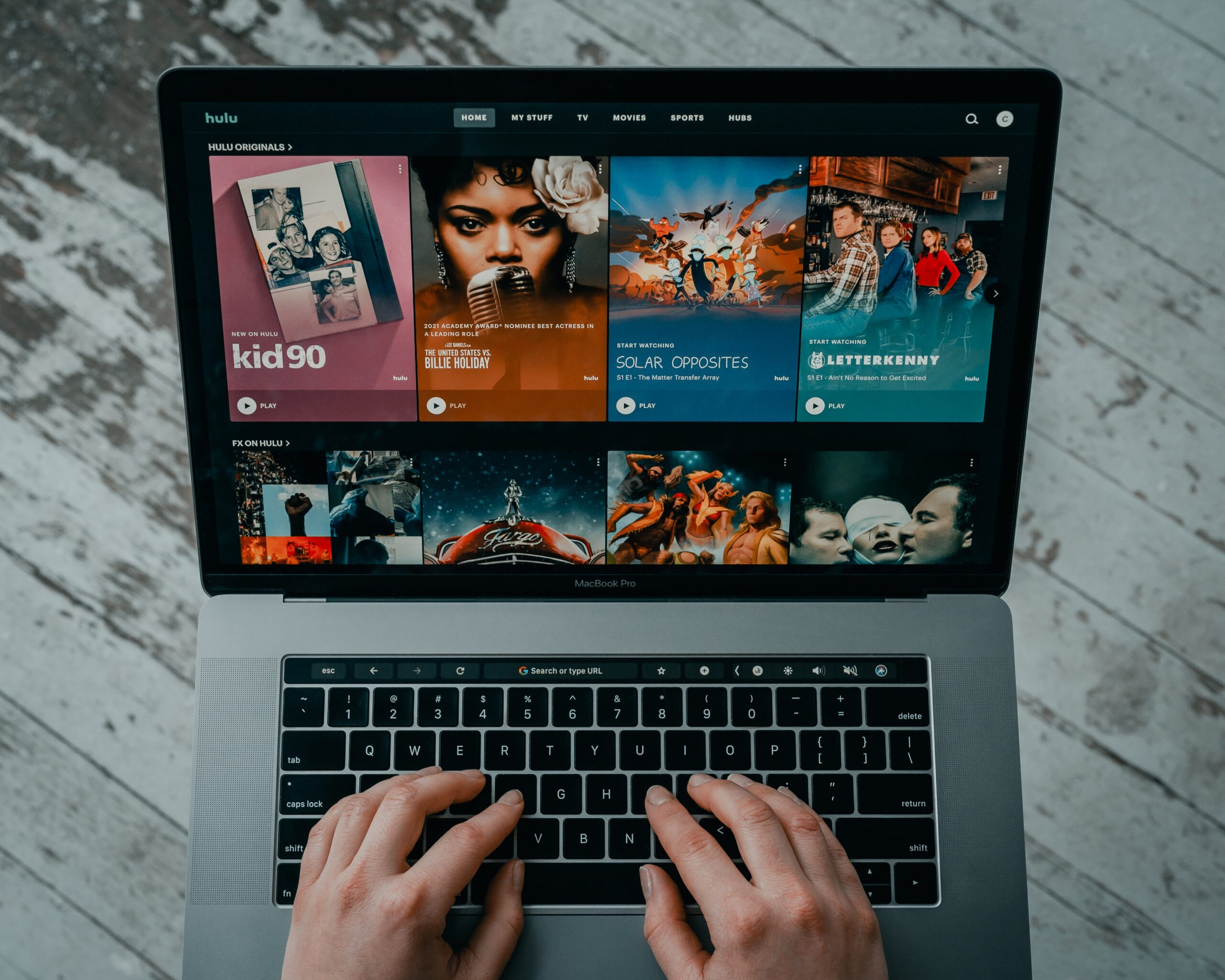 Shot from overhead, a man's hand type on a keyboard as Hulu's video catalogue appear on the screen.