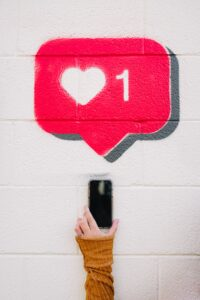 The woman holds the phone up to the white wall where one like is drawn with chalk