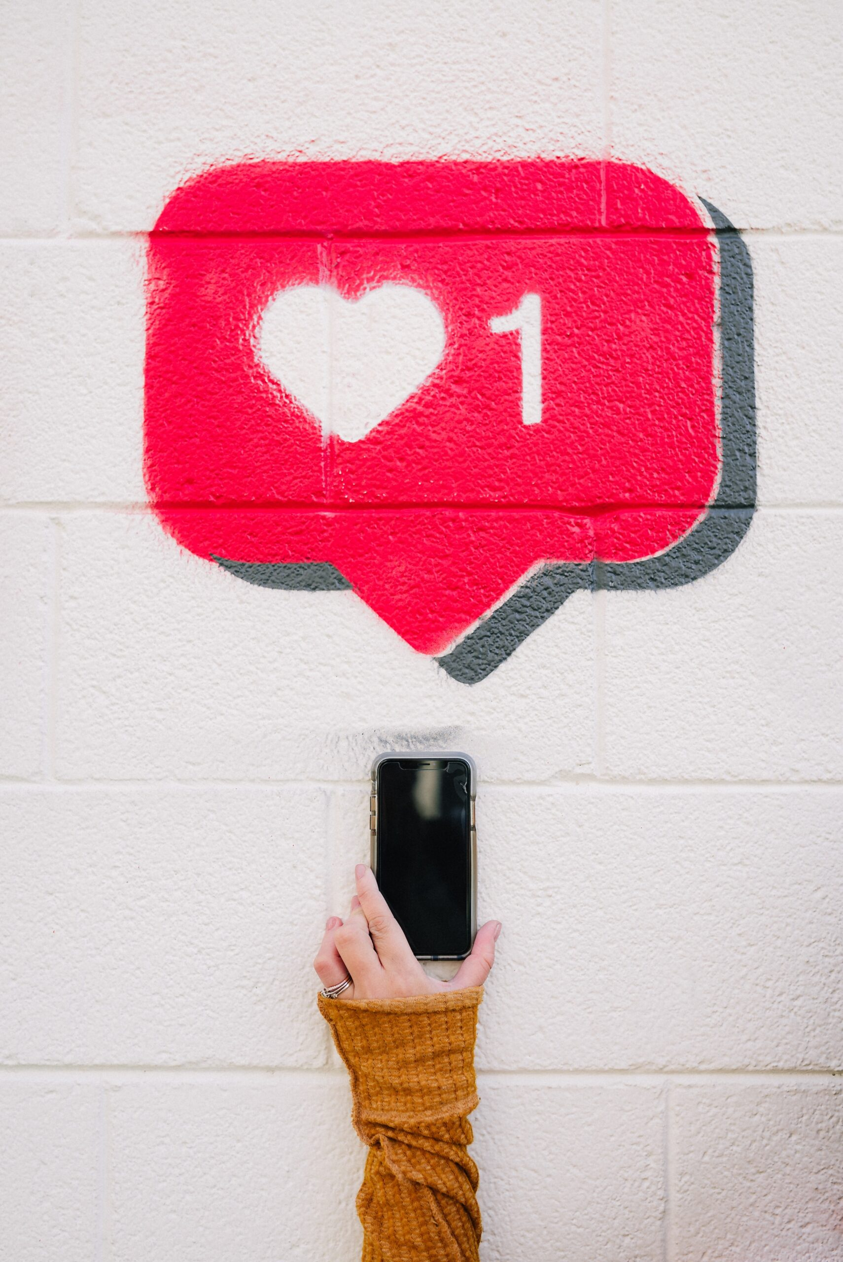 A woman holds a phone up to a white wall where 1 like is drawn on in chalk