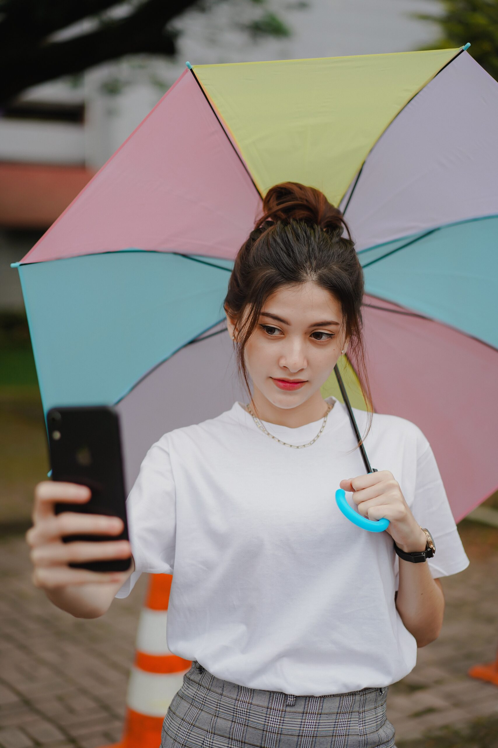A girl with an umbrella takes a selfie with a phone.