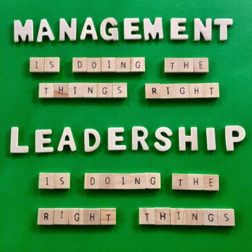 """On a green background, """"Management is doing the things right; Leadership is doing the right things,"""" appears in wood block letters."""