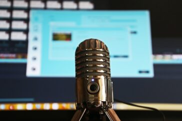 A microphone for podcasts in front of a large computer screen