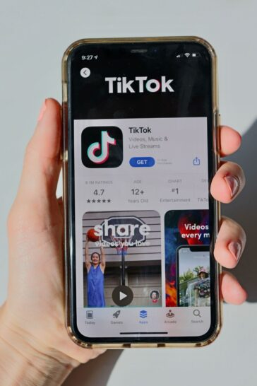 A person holds an iPhone with the TikTok app pulled up in the App Store.